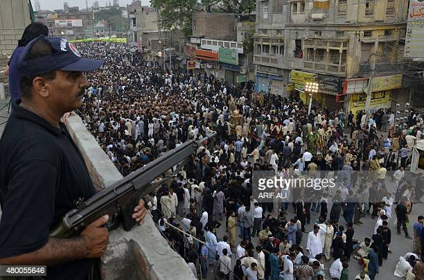 Pakistani policemen stand guard as Shiite Muslims arrive for a procession to observe the death anniversary of Imam Ali the soninlaw of Prophet...