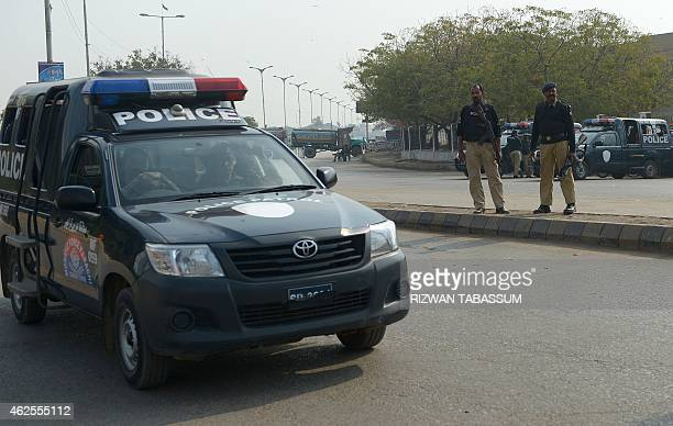 Pakistani policemen stand guard at a Shiite Muslim protest during a strike called following the deadly bomb attack at a Shiite Mosque in Shikarpur...