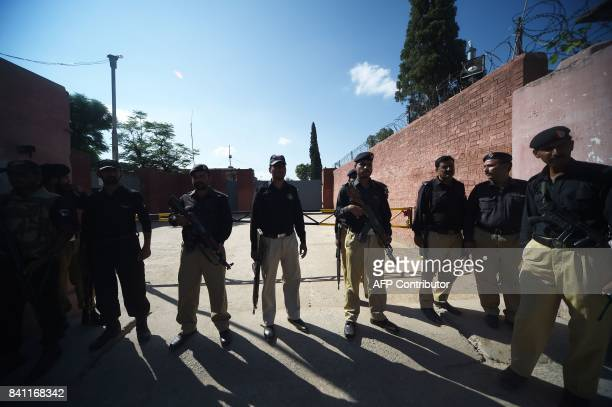 Pakistani policemen stand guard at the gate of Adyala Prison in Rawalpindi on August 31 before the announcement of the verdict in exprime minister...