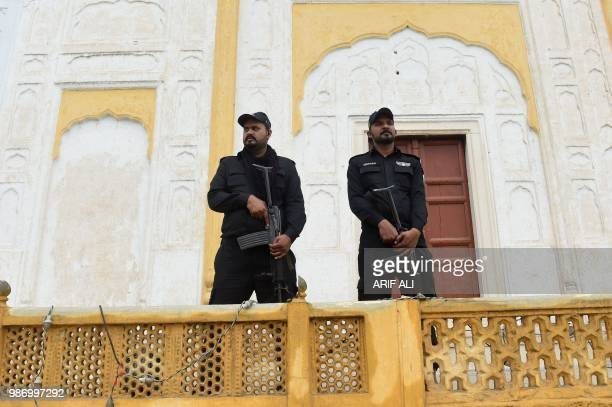 Pakistani policemen stand guard at the mausoleum of Maharaja Ranjit Singh during commemorations for his 179th death anniversary in the eastern city...