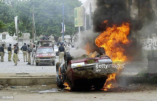 Pakistani policemen stand guard behind a burning upturned car in a street Karachi 17 August 2003 An angry mob attacked a police post ransacked an...