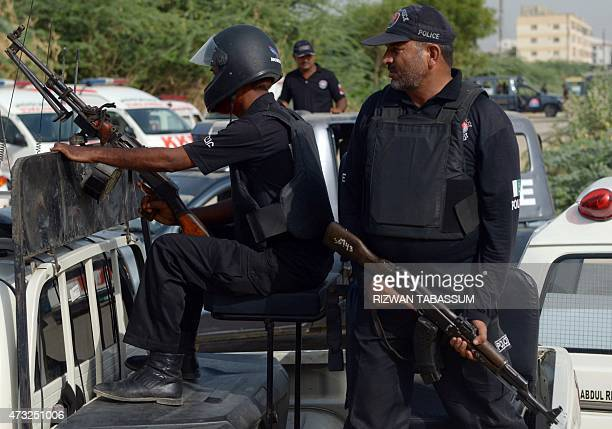 Pakistani policemen stand guard during a funeral for the victims of an attack on Pakistani Shiite Ismaili minority community members in Karachi on...