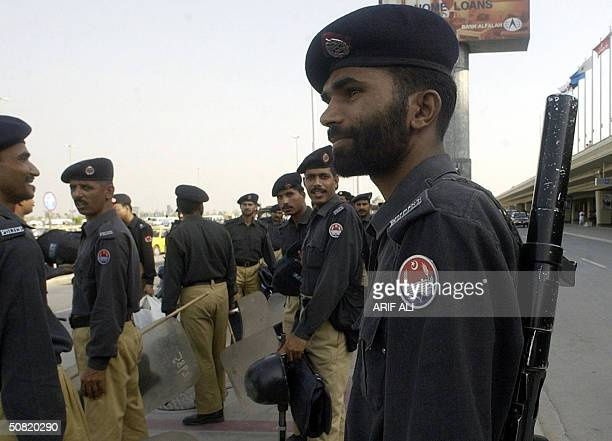 Pakistani policemen stand guard during a rehearsal at Allama Iqbal International Airport in Lahore 10 May 2004 ahead of the expected return of...