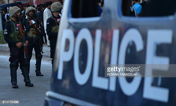 Pakistani policemen stand guard during the Ashura procession in Karachi on October 12 2016 Ashura is a period of mourning in remembrance of the...
