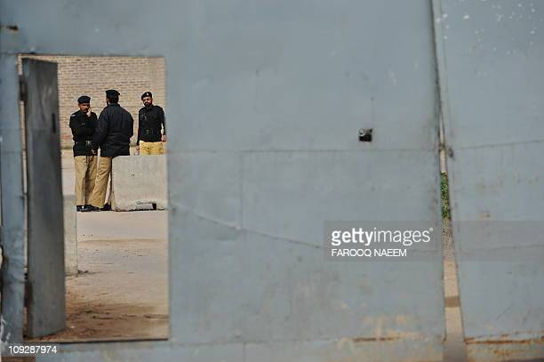 Pakistani policemen stand guard during the case hearing concering the assassination of exprime minister Benazir Bhutto at the Adiala prison in...
