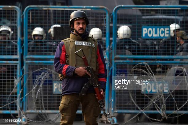 Pakistani policemen stand guard near the consulate during a demonstration following a US airstrike that killed top Iranian commander Qasem Soleimani...