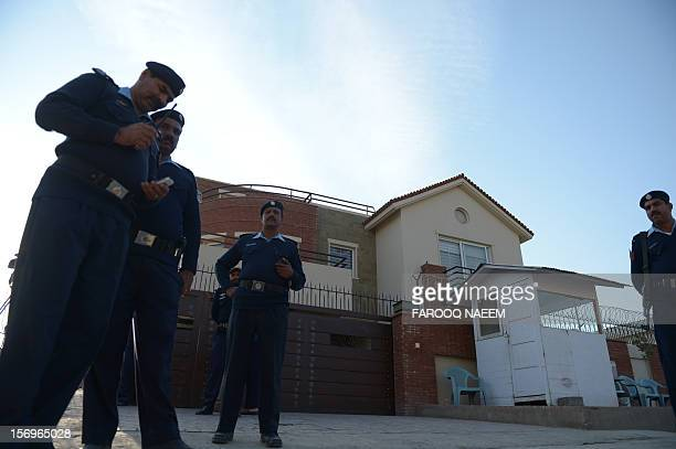 Pakistani policemen stand guard outside the house of Pakistani journalist and television anchor Hamid Mir in Islamabad on November 26 2012 A...