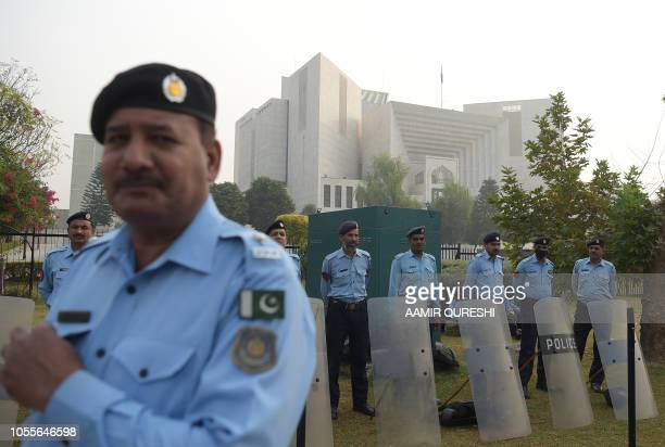 Pakistani policemen stand guard outside the Supreme Court building in Islamabad on October 31 2018 Pakistan's Supreme Court on October 31 overturned...