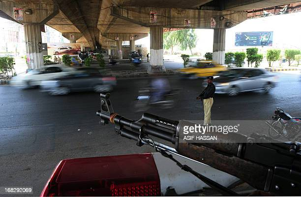 Pakistani policemen stand guard under a bridge in Karachi on May 8 2013 Pakistan goes to the polls on May 11 to elect lawmakers to the lower house of...
