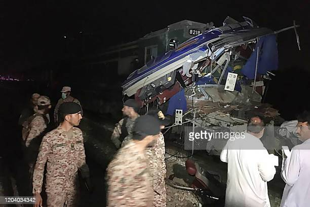 Pakistani policemen stand in front of the accident site after a passenger train hits a bus in Sukkur on February 28, 2020. - At least 14 people were...