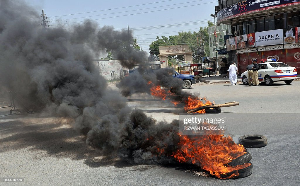 Pakistani policemen (R) stand near burning tyres torched by an angry mob during a protest against alleged target killings in Karachi on May 20, 2010. At least 17 people including two children have been killed in political clashes in Pakistan's financial capital Karachi in the past two days, a government official and police said. Police and paramilitary have been put on high alert and authorities closed all schools and colleges after the latest outbreak of politically related violence in Karachi, the biggest and richest city in Pakistan.