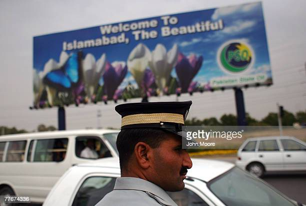 Pakistani policemen stands near a new police checkpoint on November 4 2007 at the entrance to Islamabad Pakistan On Saturday the government suspended...