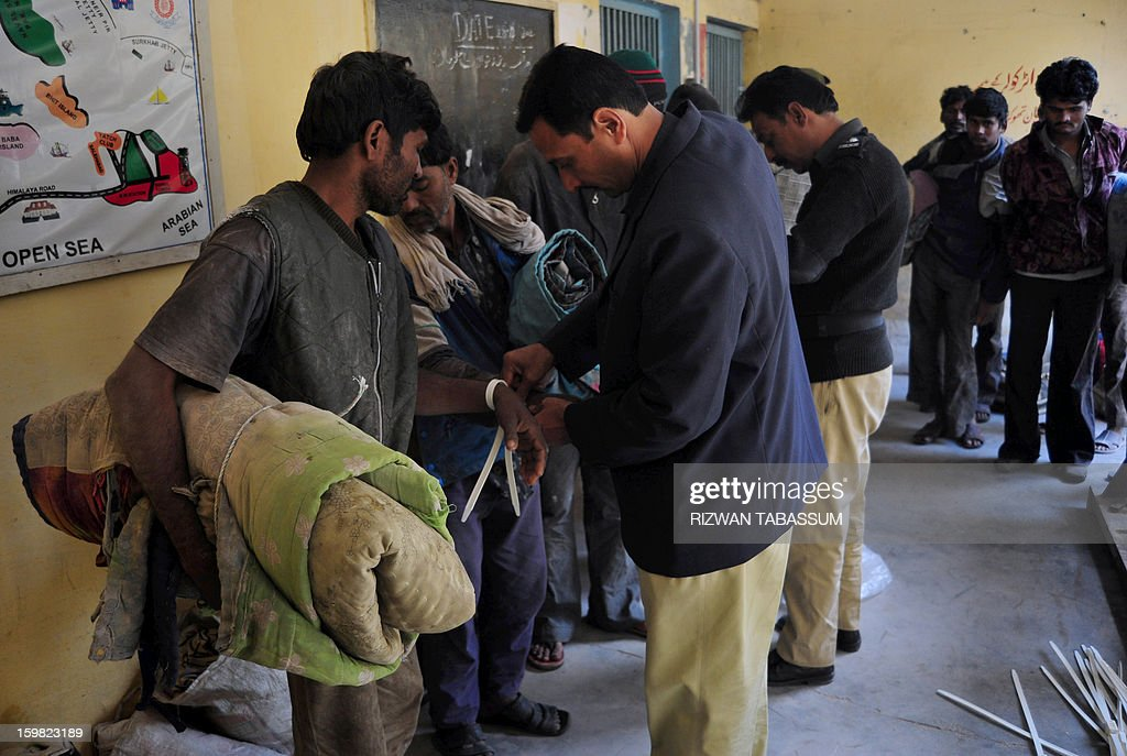 Pakistani policemen tie the hands of Indian fishermen in a police station in Karachi, on January 21, 2013. Pakistan has arrested 27 Indian fishermen for illegally straying into its territorial waters, officials said. AFP PHOTO/ Rizwan TABASSUM
