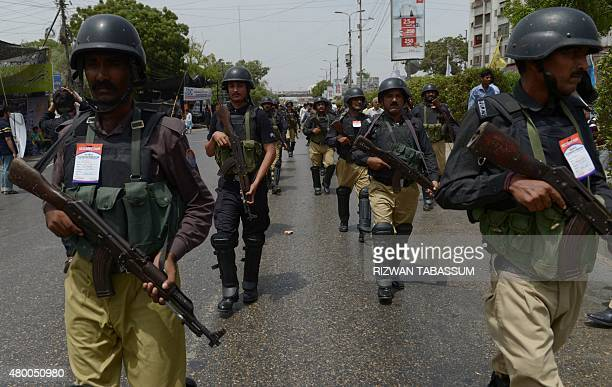Pakistani policemen walk ahead of a procession by Shiite Muslims to observe the death anniversary of Imam Ali the soninlaw of Prophet Mohammad in...