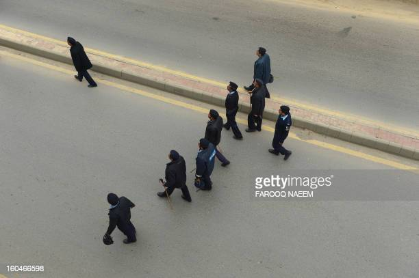 Pakistani policemen walk ahead of a protest march by activists of Ahle Sunnat Wal Jamaat in Islamabad on February 1 against the killing seminary...