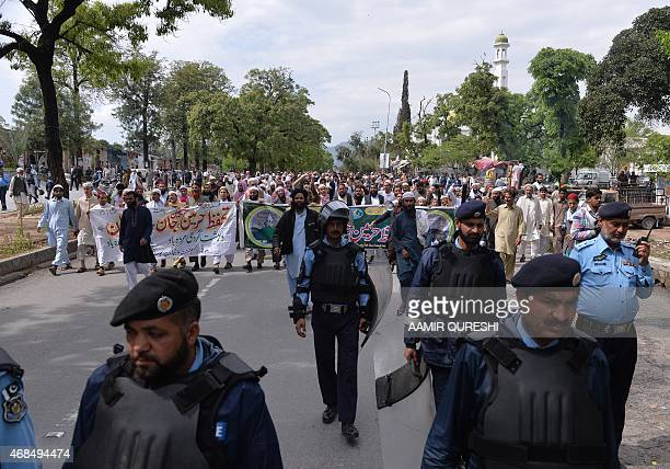 Pakistani policemen walk ahead of a rally by Sunni Muslim activists from the Ahle Sunnat Wal Jamaat in support of the government of Saudi Arabia over...