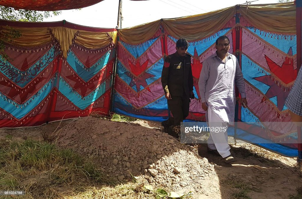 Pakistani policemen walk beside the grave of Italian national of Pakistani origin Sana Cheema who was allegedly killed by her family members in...