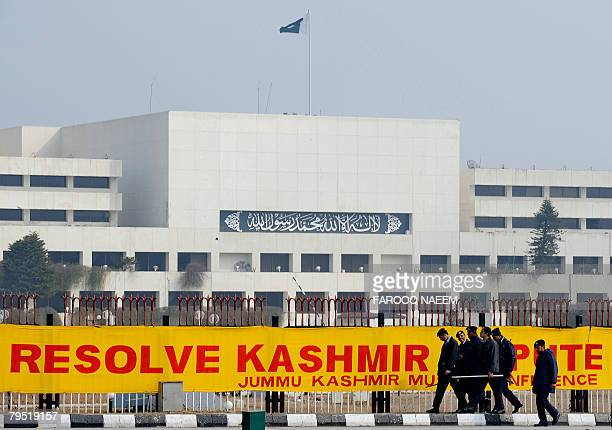 Pakistani policemen walk past a banner in front of the National Assembly in Islamabad on February 5 2008 The Kashmir Solidarity Day was observed in...