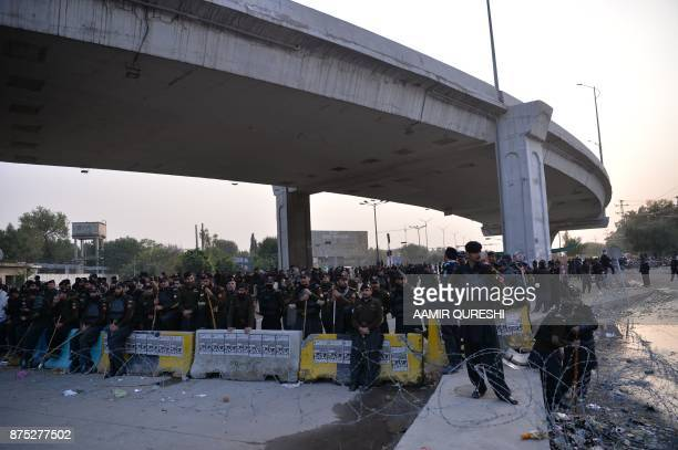 Pakistani policemen watch the activists of the TehreekiLabaik Yah Rasool Allah Pakistan religious group at a blocked street during a week long...