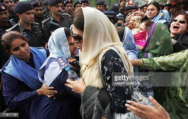 Pakistani policewomen scuffle with the supporters of former Pakistani prime minister Benazir Bhutto during a protest outside the Bhutto residence in...