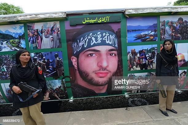 Pakistani policewomen stand guard beside a poster bearing the image of slain Indian Kashmir Hizbul Mujahideen commander Burhan Wani which adorns...