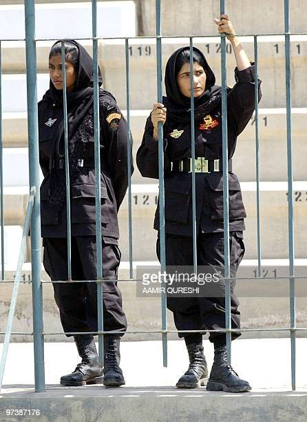 Pakistani policewomen watch the practice session of Pakistani and Indian cricket teams at Multan Cricket Ground in Multan 27 March 2004 India's...