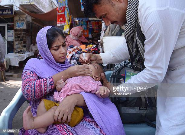 "Pakistani Polio Vaccination Team administering polio drops to children during ""Anti-polio campaign"" at suburb.The World Health Organization said that..."