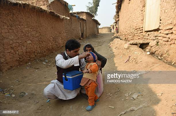 Pakistani polio vaccination worker Sher Khan administers polio vaccine to a child in a poor neighbourhood that hosts Afghan refugees and internally...