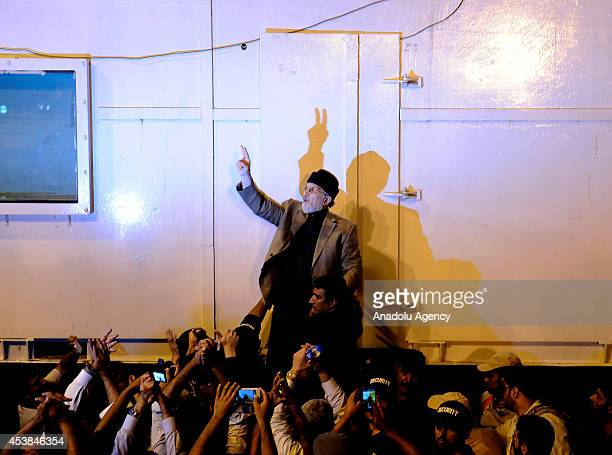 Pakistani political party Pakistan Awami Tehreek leader Tahir ulQadri flashes victory sign to his supporters in front of the parliament building...