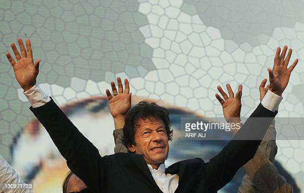 Pakistani politician and former cricketer Imran Khan gestures upon his arrival during a rally in Lahore on October 30 2011 A crowd of thousands...