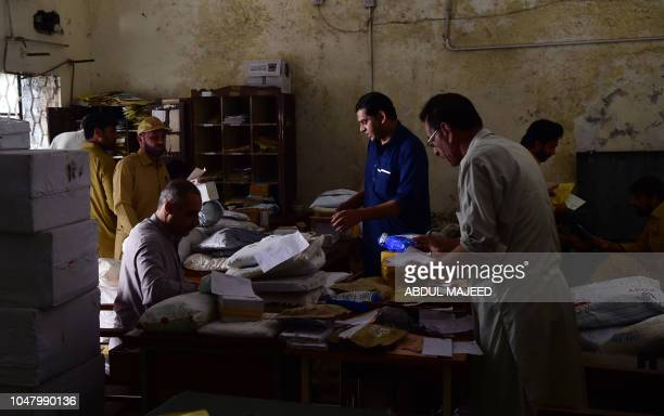 Pakistani postal workers arrange posts at a post office during World Post Day in Peshawar on October 9 2018 World Post day is marked every year on...