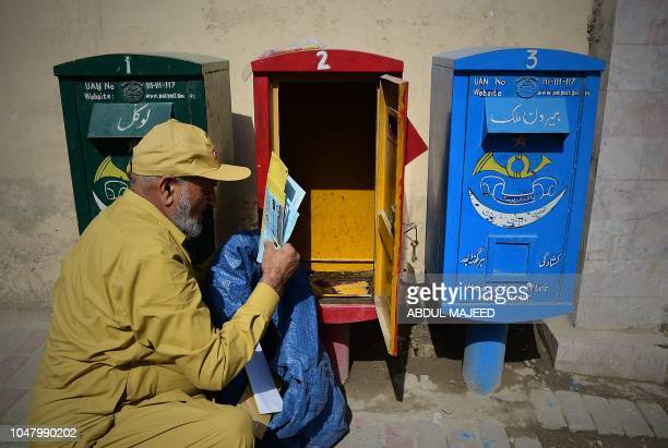 A Pakistani postman collects posts from a post box during World Post Day in Peshawar on October 9 2018 World Post day is marked every year on October...