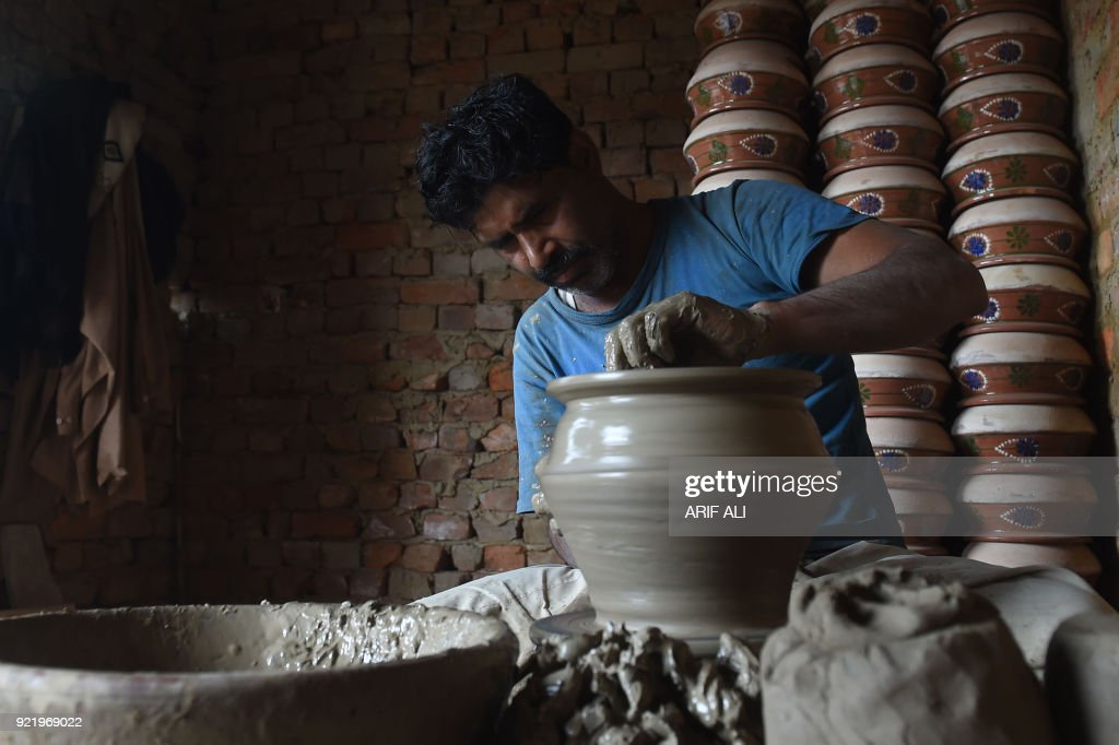 A Pakistani potter makes an earthen pot at his workshop on the outskirts of Lahore on February 21, 2018. Hundreds of Pakistani potters, locally known as Kumhars, manufacture the earthen pots in rural and suburban areas of Pakistan, which are mostly used for cooking and as decoration pieces. /