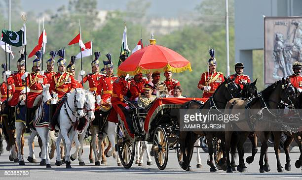 Pakistani President Pervez Musharraf salutes as he rides in a horsedrawn carriage escorted by presidential guards while he arrives at the venue of...