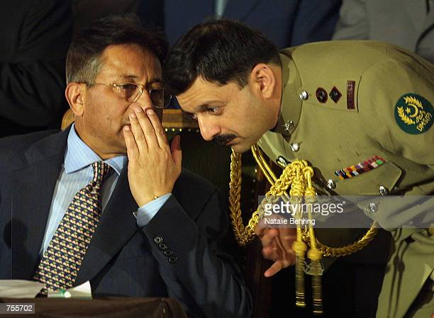 Pakistani President Pervez Musharraf speaks with a military official during a briefing with Afghan Interim leader Hamid Karzai April 2 2002 in Kabul...