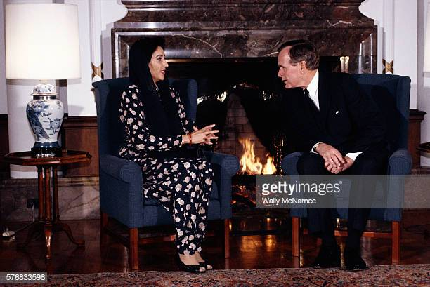 Pakistani Prime Minister Benazir Bhutto and US President George Bush talk in front of a fireplace at the US Embassy in Tokyo
