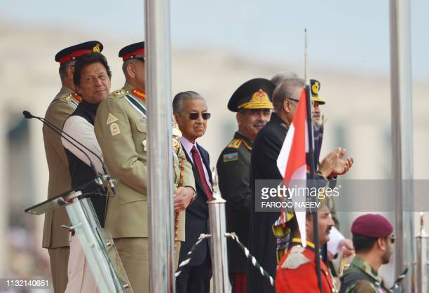 Pakistani Prime Minister Imran Khan and his Malaysia's counterpart Mahathir Mohamad along with other officials look at a jets performing during the...