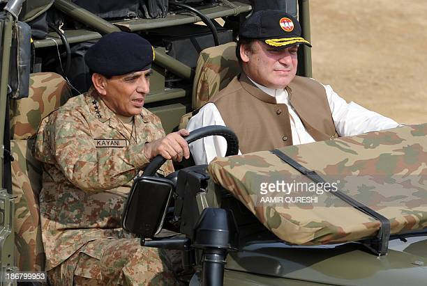 Pakistani Prime Minister Nawaz Sharif sits in the front passenger seat as Pakistani Army Chief General Ashfaq Kayani drives an army vehicle to take...