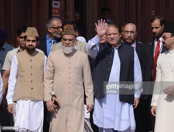 Pakistani Prime Minister Nawaz Sharif waves as he walks with Syed Ahmed Bukhari the Shahi Imam of the 17th century Jama Masjid during his visit to...