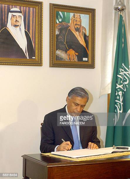 Pakistani Prime Minister Shaukat Aziz signs a condolence book at the Saudi embassy in Islamabad 03 August 2005 below portraits of the late King Shah...