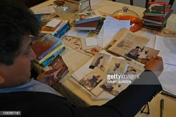 Pakistani prominent journalist Hamid Mir shows his photograph along with Osama Bib Laden, the slain former leader of Al Qaeda when he interviewed him...