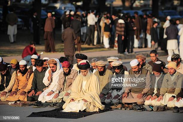 Pakistani proTaliban cleric Abdul Aziz leads a prayer with tribesmen of north Waziristan on a street in Islamabad on December 10 on the second day of...