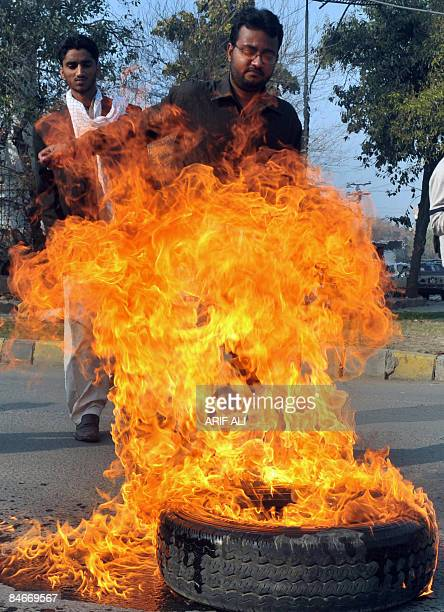 A Pakistani protester burns tyres on a street during a protest against the killing of the Shiite Muslims in Lahore on February 6 2009 Pakistani...