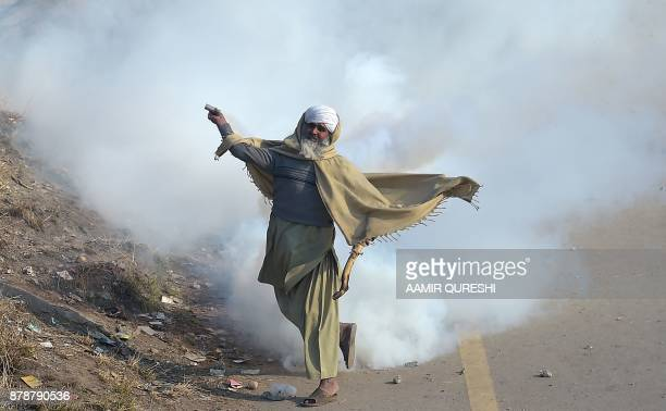 Pakistani protester of the TehreekiLabaik Yah Rasool Allah Pakistan religious group throws a tear gas shell back towards police during a clash in...