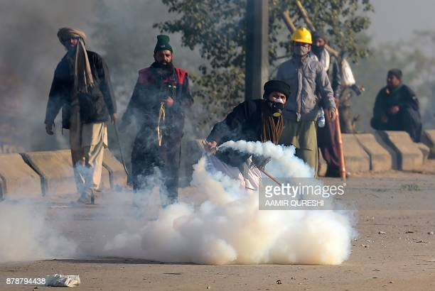 A Pakistani protester of the TehreekiLabaik Yah Rasool Allah Pakistan religious group throws a tear gas shell back towards police during a clash in...