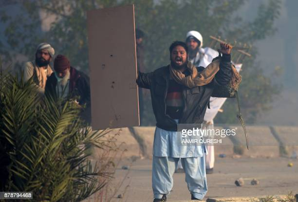 A Pakistani protester of the TehreekiLabaik Yah Rasool Allah Pakistan religious group shout slogans during a clash in Islamabad on November 25 2017...