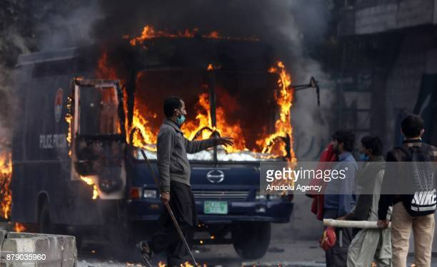 Pakistani protesters are seen beside a burning police van which was set on fire by them after security forces launched a crackdown on Saturday...