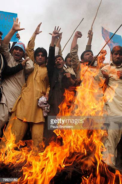 Pakistani protesters burn a Danish flag to show their anger against the reprinting of a cartoon depicting the Prophet Muhammad in Danish newspapers...