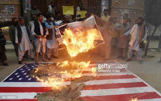 Pakistani protesters burn a US flag and a banner bearing an image of the US President Donald Trump during a demonstration against a US airstrike in...