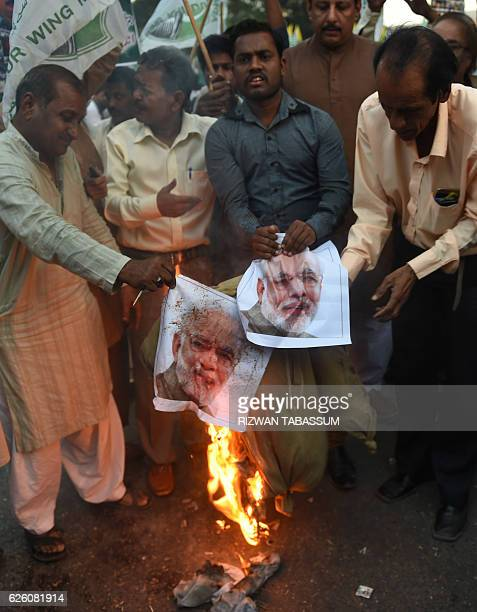Pakistani protesters burn an effigy and a poster bearing the image of Indian Prime Minister Narendra Modi during a demonstration in Karachi on...